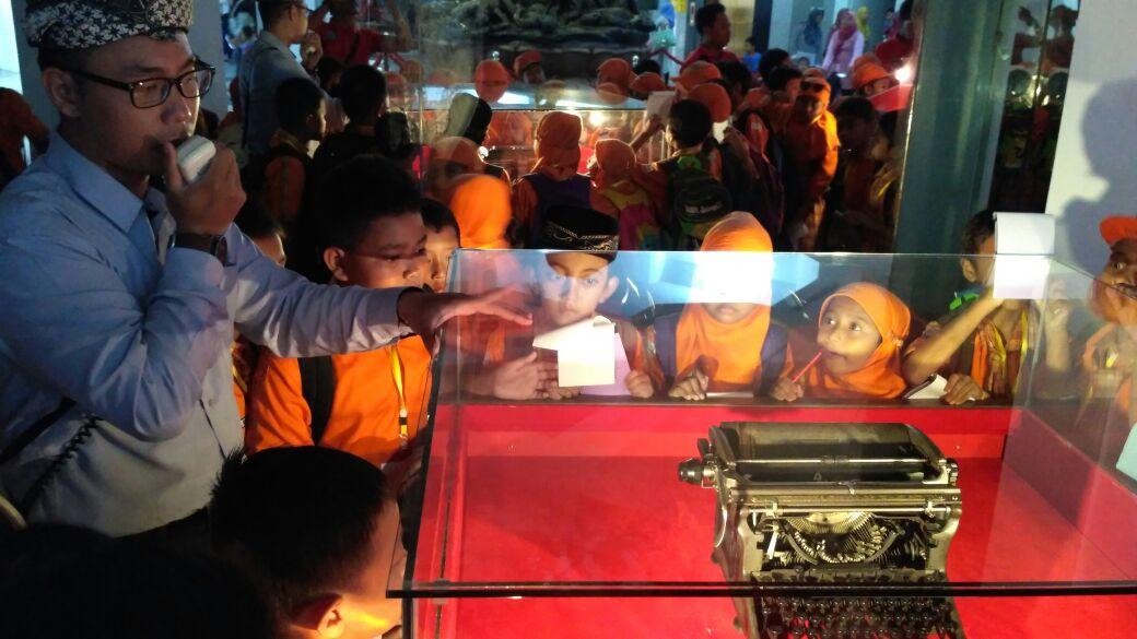 Siswa-siswi sedang mengamati mesin ketik dan mendengarkan pengarahan