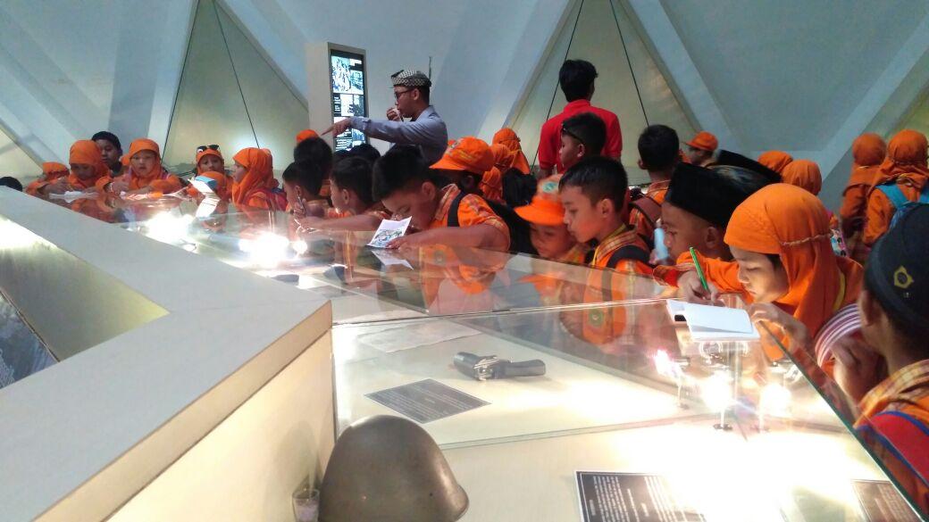 Siswa-siswi sedang mengamati benda peninggalan pahlawan dan mendengarkan pengarahan